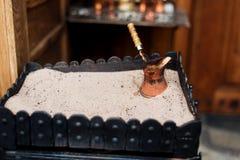 Stäng sig upp sikten av turkiskt kaffe som är förberedd på varm guld- sand royaltyfri bild