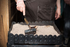 Stäng sig upp sikten av turkiskt kaffe som är förberedd på varm guld- sand arkivbild