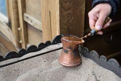 Stäng sig upp sikten av turkiskt kaffe som är förberedd på varm sand Royaltyfria Foton