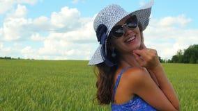 Stäng sig upp skott av att le den caucasian kvinnan i den vita hatten i det gröna fältet lager videofilmer