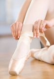 Stäng sig upp skott av ben av ballerina som snör åt pointesna royaltyfria bilder