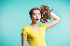 Stäng sig upp skott av den stilfulla unga kvinnan som ler mot blå bakgrund Härlig kvinnlig modell samlade hårhänder och blickar m fotografering för bildbyråer