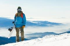 Stäng sig upp skott av den unga snowboarderen i hjälmen som upptill står av ett berg på den guld- timmen med hans snowboard i han Arkivfoto