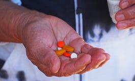 Stäng sig upp skott av en hand som rymmer flera mediciner Arkivfoton