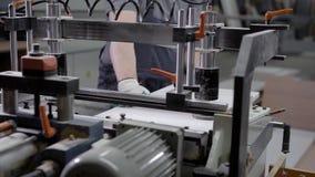 Stäng sig upp skott av en man som fungerar på maskinen för trä på en fabrik arkivfilmer