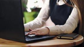 Stäng sig upp skott av en maskinskrivningtext för ung kvinna på en bärbar dator lager videofilmer