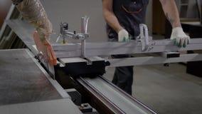 Stäng sig upp skott av ett driftigt träbräde för två industriarbetare till och med den bitande maskinen lager videofilmer