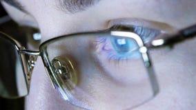 Stäng sig upp skott av flickan i exponeringsglas som surfar internet på natten Arkivfoton