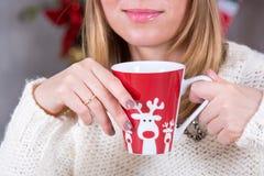 Stäng sig upp skott av koppen i händer av kvinnan med den varma drinken på julgranbakgrund, lyckligt feriebegrepp Royaltyfri Bild