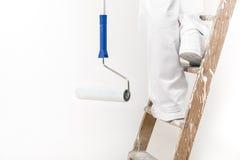 Stäng sig upp skott av målaren som mannen på arbete som klättrar en stege med, smärtar arkivbilder