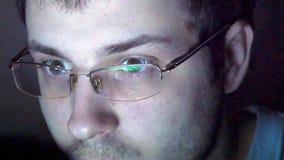 Stäng sig upp skott av mannen i exponeringsglas som surfar internet på natten Arkivfoton