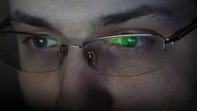 Stäng sig upp skott av mannen i exponeringsglas som surfar internet på natten Arkivbild