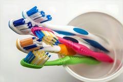 Stäng sig upp skott av uppsättningen av mångfärgade tandborstar i exponeringsglas på cl Arkivbild