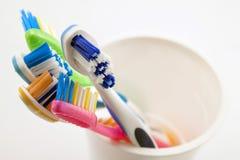 Stäng sig upp skott av uppsättningen av mångfärgade tandborstar i exponeringsglas på cl Arkivbilder
