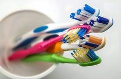 Stäng sig upp skott av uppsättningen av mångfärgade tandborstar i exponeringsglas på cl Royaltyfria Bilder