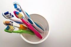 Stäng sig upp skott av uppsättningen av mångfärgade tandborstar i exponeringsglas på cl Royaltyfria Foton