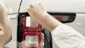 Stäng sig upp skottet av händerna av en man som skalar filmen från en vit bil lager videofilmer