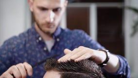 Stäng sig upp skottet av huvudet av en man som kammar hans hår och gör en innegrej som utformar i frisersalong med en hårkam och  stock video