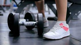 Stäng sig upp skottet av idrotts- lyftande hantlar för den unga kvinnan på idrottshallen Royaltyfria Bilder