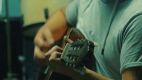 Stäng sig upp skottet av musikern som sjunger och spelar gitarren stock video