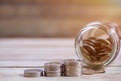 Stäng sig upp sparande pengar in i en exponeringsglaskrus för framtid för kassa in för att investera royaltyfri bild