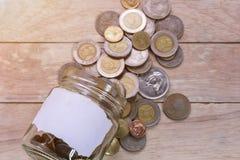 Stäng sig upp sparande pengar in i en exponeringsglaskrus för framtid för kassa in för att investera royaltyfri foto