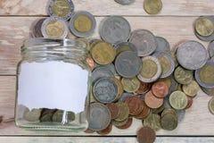 Stäng sig upp sparande pengar in i en exponeringsglaskrus för framtid för kassa in för att investera royaltyfria bilder