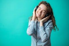 Stäng sig upp ståenden av att le den ljust rödbrun flickan som tycker om sången i hörlurar fotografering för bildbyråer
