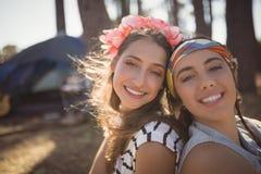 Stäng sig upp ståenden av att le vänner som sitter på fält mot tältet Royaltyfri Foto