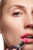 Stäng sig upp ståenden av attraktiva kanter av den härliga kvinnan Rouging hennes kanter med rosa färgkompisläppstift Damen ler f Arkivbilder