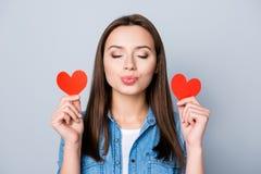 Stäng sig upp ståenden av brunettflickan som rymmer två lilla röda hjärtor royaltyfria bilder