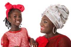Stäng sig upp ståenden av den afrikanska kvinnan med lilla flickan i röda kläder för tradition royaltyfri bild