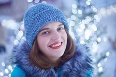 Stäng sig upp ståenden av den angenäma seende unga kvinnan med blåa ögon, röda kanter, sund hud, bär den varma stack hatten, och  Royaltyfri Bild