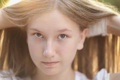 Stäng sig upp ståenden av den attraktiva tonåriga flickan i solnedgång arkivbild