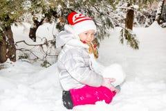 Stäng sig upp ståenden av den förtjusande lyckliga lilla flickan som lyckligt grinar på kameran på en solig dag för vinter` s royaltyfri bild