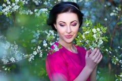Stäng sig upp ståenden av den härliga kvinnan i blommande gar för körsbärsrött träd Arkivfoton