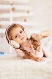 Stäng sig upp ståenden av den härliga lilla flickan i öronskydd Arkivbild