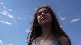 Stäng sig upp ståenden av den härliga unga flickan med att blåsa hår i vind stock video