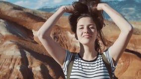 Stäng sig upp ståenden av den härliga unga kvinnan i natur med brunetthår som blåser i vind som ser fotvandraren för bergsikten stock video