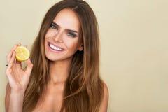 Stäng sig upp ståenden av den hållande citronen för den attraktiva brunettkvinnan Royaltyfri Fotografi
