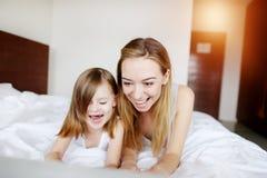 Stäng sig upp ståenden av den toppna lyckliga moder- och dotterfamiljen med att le för bärbar dator arkivfoton