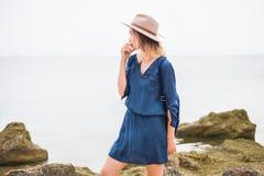 Stäng sig upp ståenden av den unga kvinnan i den utomhus- bruna hatten ha gyckel på havet royaltyfri foto