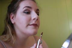 Stäng sig upp ståenden av den unga kvinnan med röda kanter Härlig kvinna som gör daglig makeup Applicera för läppstift royaltyfria foton