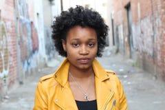 Stäng sig upp ståenden av en attraktiv ung svart kvinna med afro hår royaltyfri fotografi