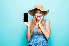 Stäng sig upp ståenden av en gladlynt ung kvinna i klänningen och sommarhatten som visar mobiltelefonen för den tomma skärmen öve royaltyfri foto