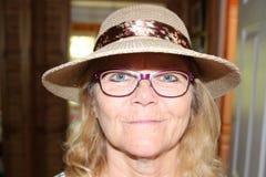 Stäng sig upp ståenden av en härlig äldre hög kvinna som ler med hatten royaltyfri fotografi