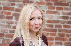 Stäng sig upp ståenden av en härlig blond flicka över den röda väggen Royaltyfria Bilder