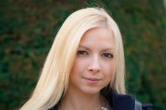 Stäng sig upp ståenden av en härlig blond flicka över grönt suddigt Fotografering för Bildbyråer