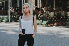 Stäng sig upp ståenden av en le ung flicka med kaffe Arkivbild