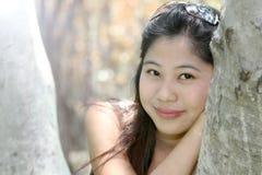 Stäng sig upp ståenden av en ung asiatisk kvinna i en parkera Royaltyfria Bilder